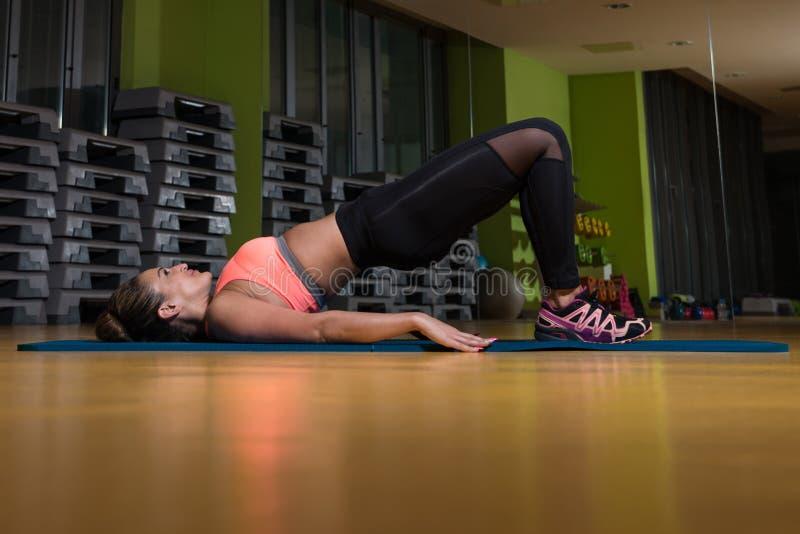 Junge Frau, die Übung auf Foor-Beinen tut stockbilder