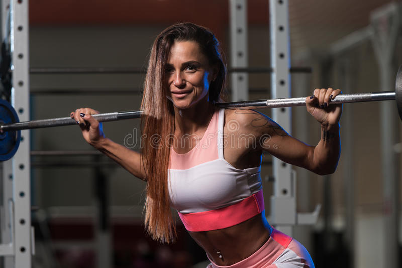 Junge Frau, die Übung mit Barbell-Hocke tut lizenzfreies stockfoto