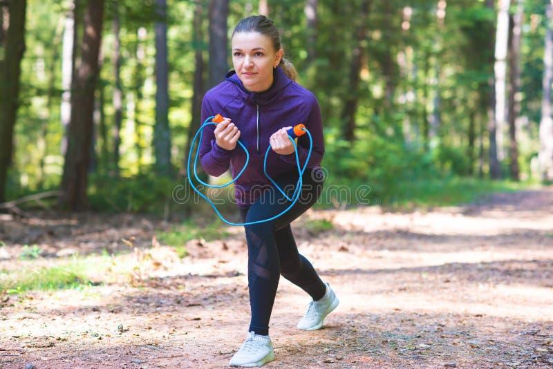 Junge Frau, die Übungen im sonnigen Wald rüttelt und macht lizenzfreie stockfotos