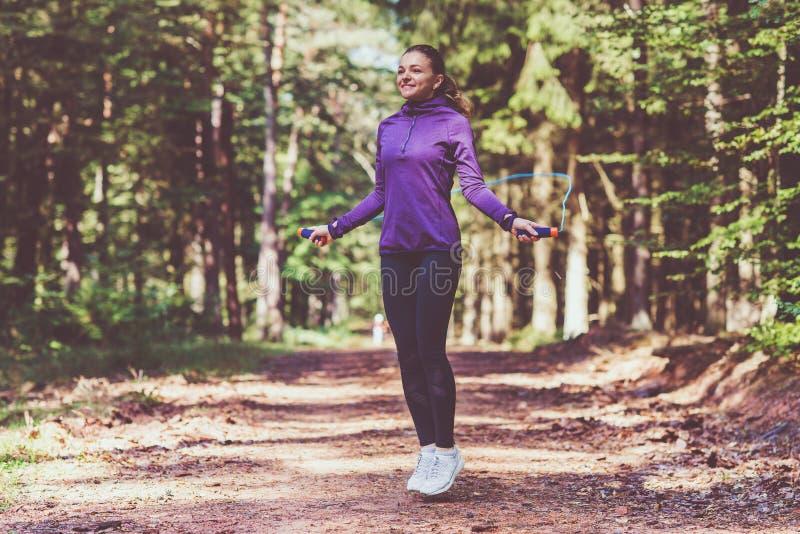 Junge Frau, die Übungen im sonnigen Wald rüttelt und macht stockfotos