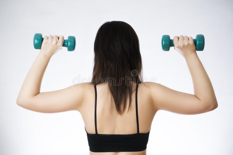 Junge Frau, die Übungen mit Dummköpfen tut lizenzfreie stockfotografie