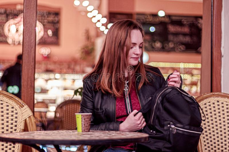 Junge Frau, die am Abend in einem Café sitzt und schaut, um Rucksack zu schwärzen stockfotografie