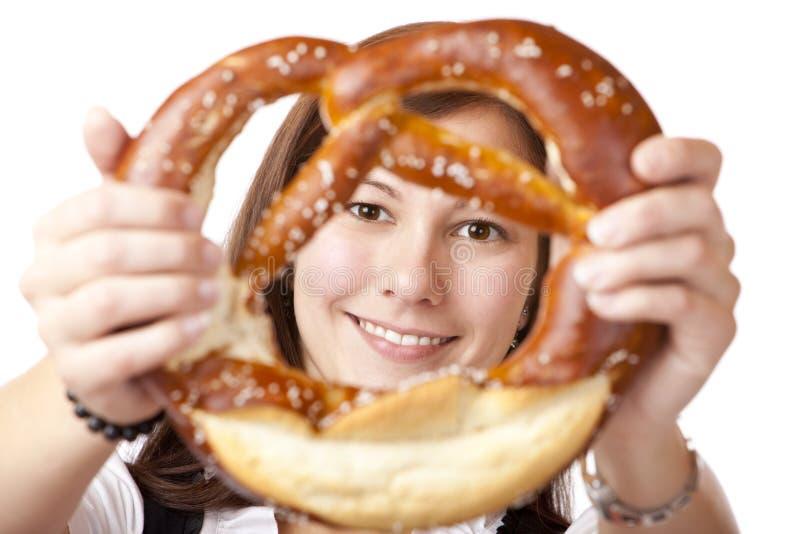 Junge Frau, die Abflussrinne Oktoberfest Brezel schaut. lizenzfreies stockfoto