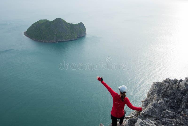 Junge Frau, die allein auf dem Klippenrand und -ihr tun Sieg p steht stockbild