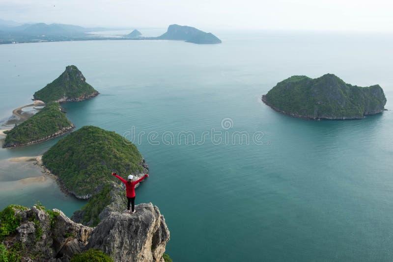 Junge Frau, die allein auf dem Klippenrand und -ihr tun Sieg p steht lizenzfreie stockfotografie