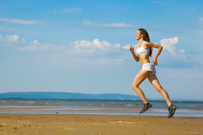 Junge Frau, die alleine auf den Strand läuft stockfotografie