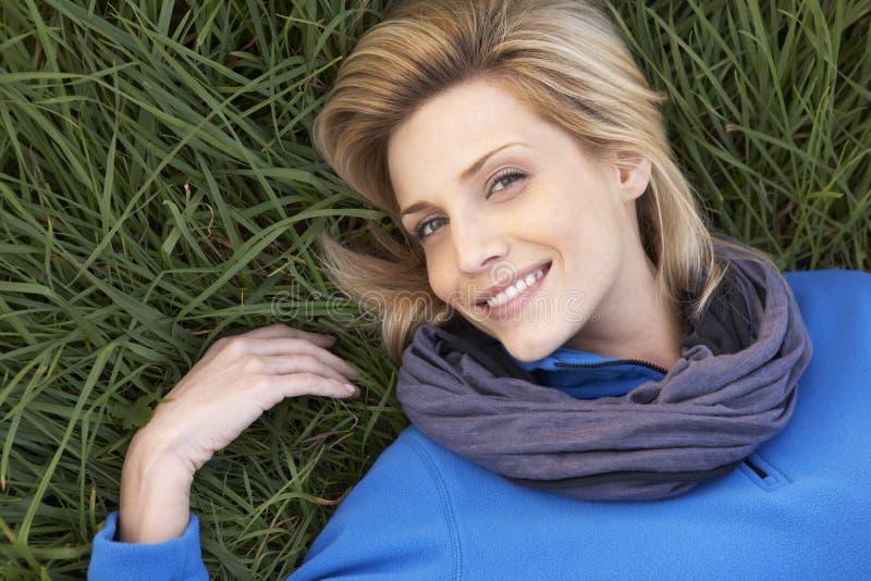 Junge Frau, die alleine auf Gras liegt stockfoto