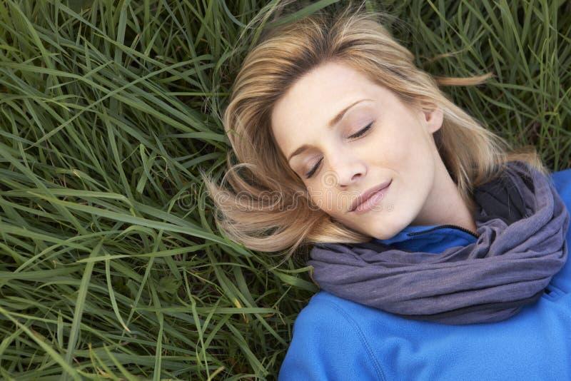 Junge Frau, die alleine auf Gras Nickerchen macht stockfotos
