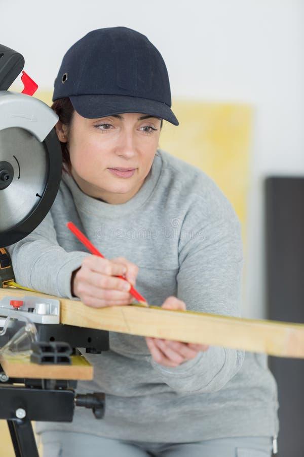 Junge Frau, die als hölzerner Erbauer arbeitet stockfoto