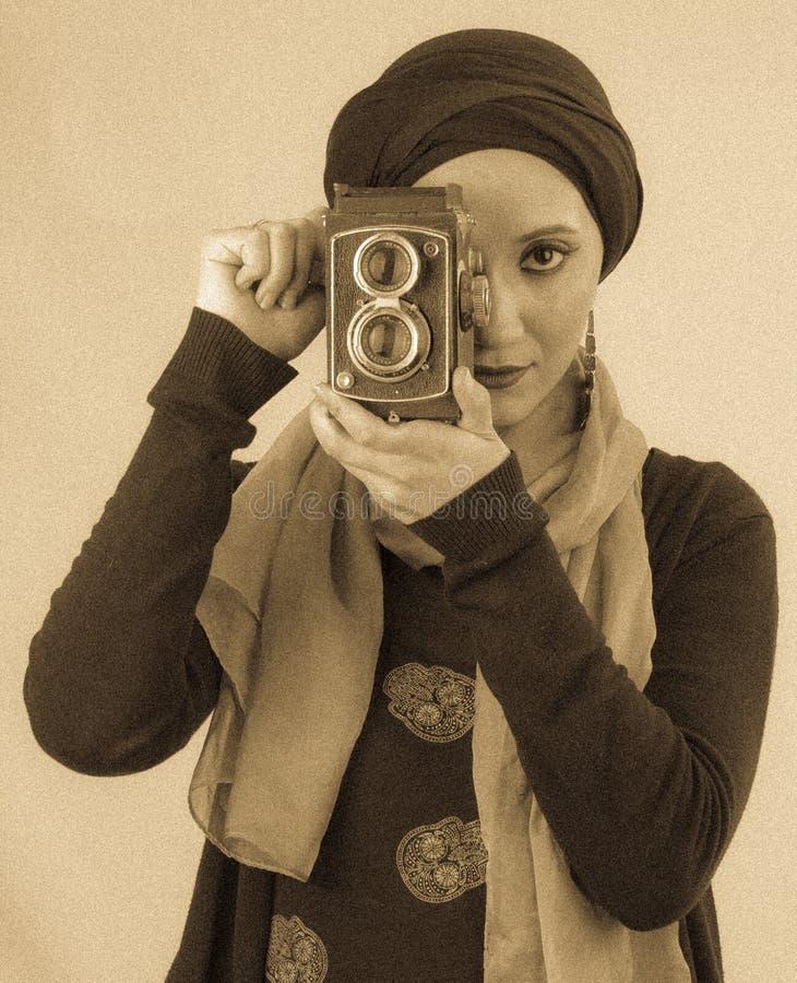 Junge Frau, die alte Kamera im hijab und im bunten Schal hält stockfotografie