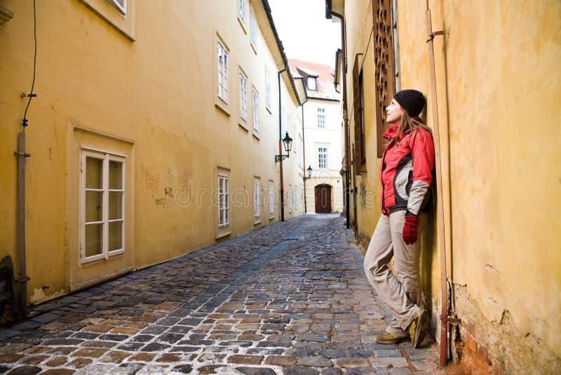 Junge Frau, die in alte Stadt geht stockfoto