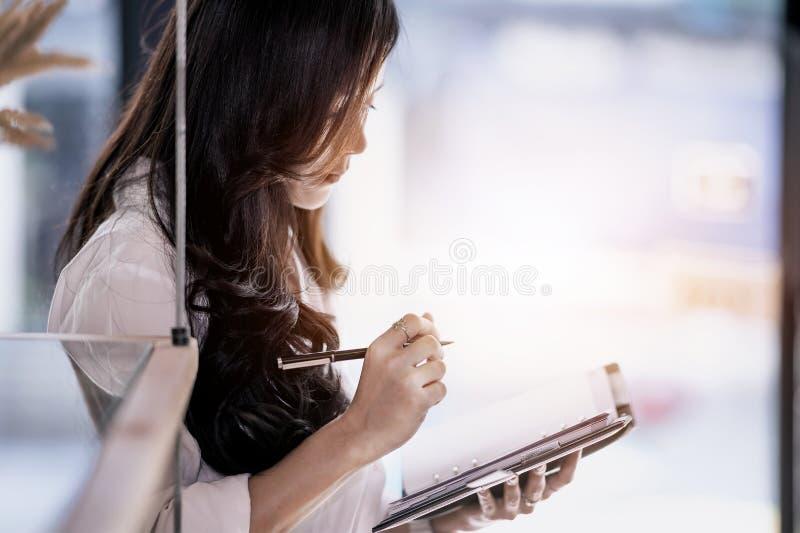 Junge Frau, die Anmerkungen zu ihrem Tagebuch steht und macht stockbilder