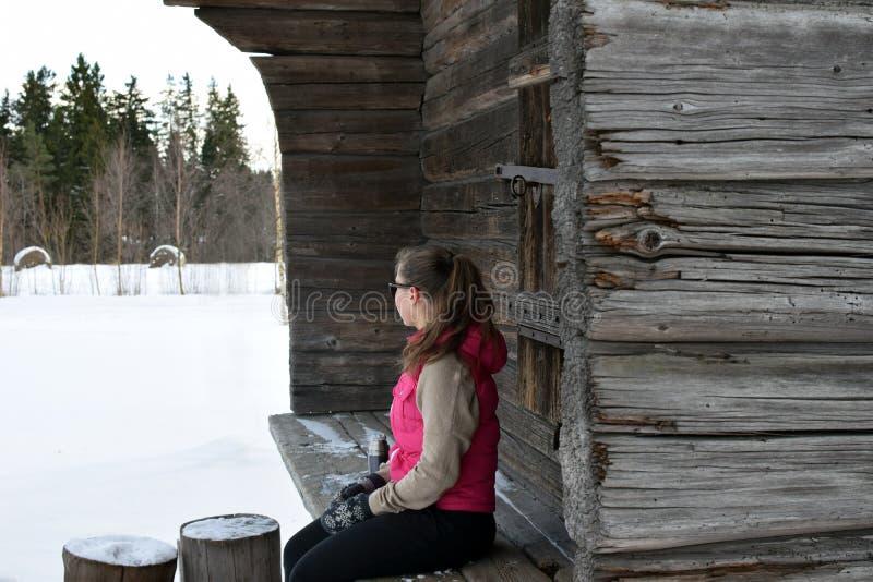 Junge Frau, die außerhalb des alten Blockhauses sitzt lizenzfreies stockbild