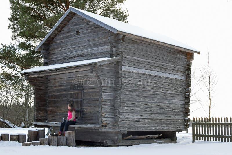 Junge Frau, die außerhalb des alten Getreidespeichers sitzt stockbilder
