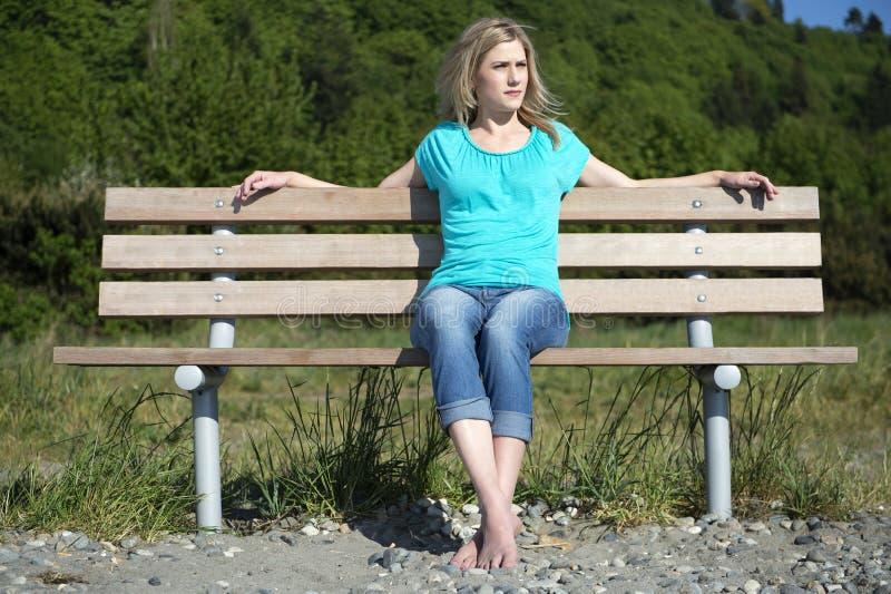 Junge Frau, die auf Bank am Strand sitzt lizenzfreie stockbilder