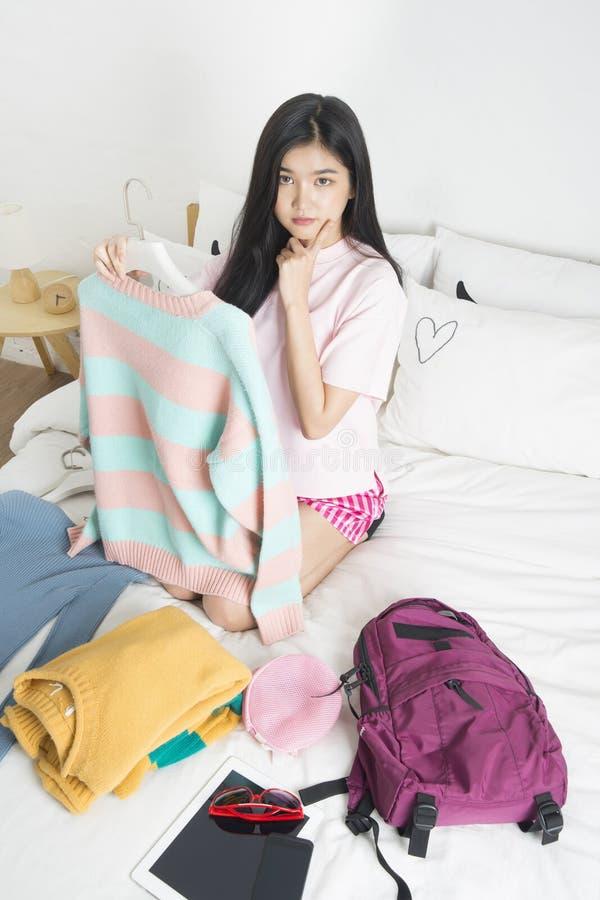 Junge Frau, die auf Bett beim Denken sitzt stockfoto