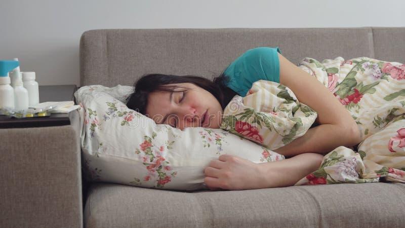 Junge Frau, die auf Bett mit Erkältung liegt lizenzfreie stockfotografie