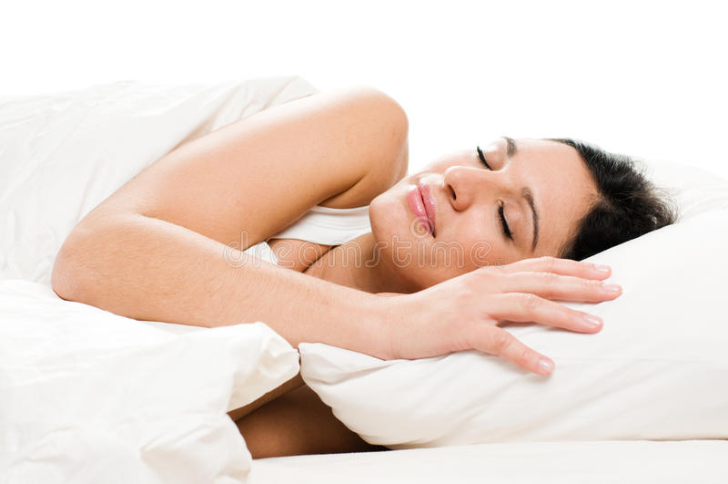 Junge Frau, die auf Bett schläft lizenzfreies stockfoto