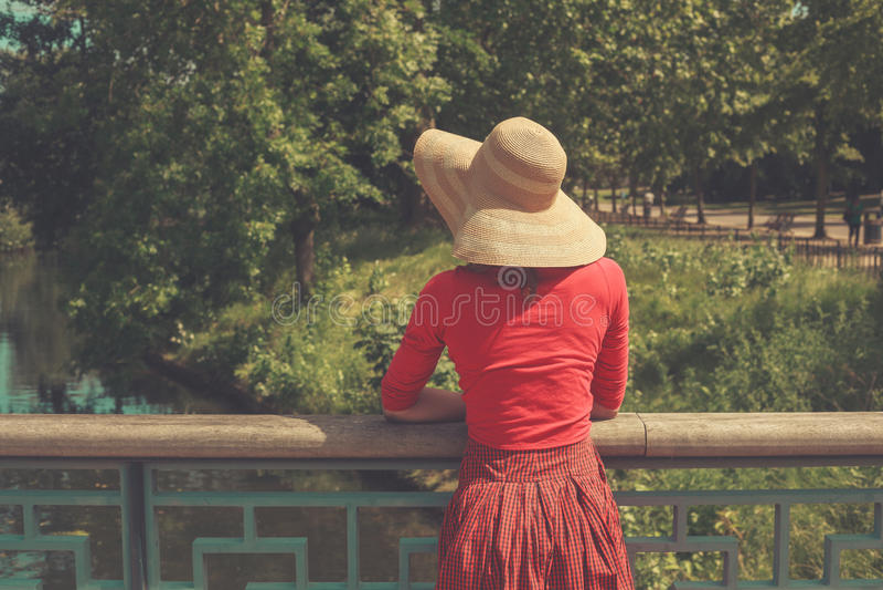Junge Frau, die auf Brücke steht und Wasser betrachtet stockbilder