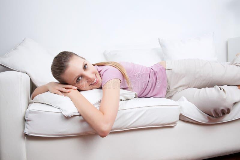 Junge Frau, die auf Couch liegt stockfotografie