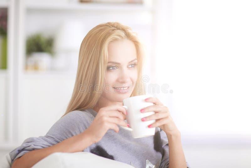 Junge Frau, die auf Couch und trinkendem Tee im hellen Raum stillsteht lizenzfreies stockbild