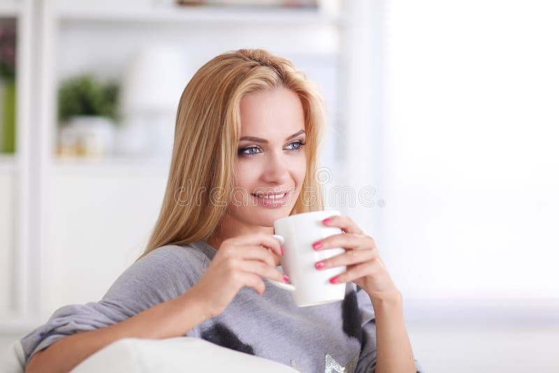 Junge Frau, die auf Couch und trinkendem Tee im hellen Raum stillsteht lizenzfreie stockbilder