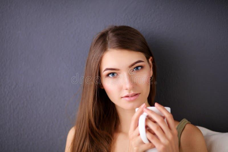 Junge Frau, die auf Couch und trinkendem Tee im Raum stillsteht stockfoto