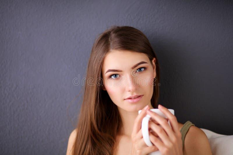 Junge Frau, die auf Couch und trinkendem Tee im Raum stillsteht lizenzfreies stockbild