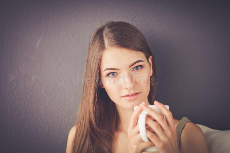 Junge Frau, die auf Couch und trinkendem Tee im Raum stillsteht lizenzfreie stockbilder