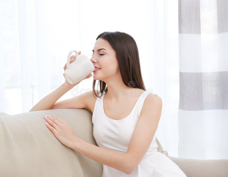 Junge Frau, die auf Couch und trinkendem Tee stillsteht lizenzfreie stockfotos