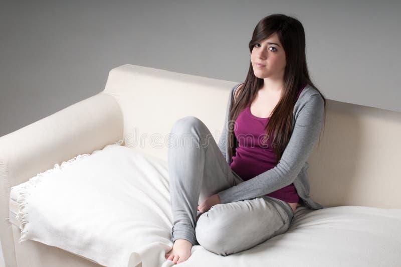Junge Frau, die auf Couchausgangsinnenraum sitzt. lizenzfreies stockbild