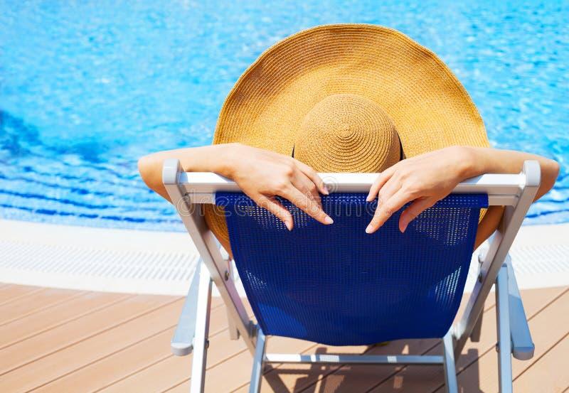 Junge Frau, die auf deckchair durch Swimmingpool liegt lizenzfreie stockfotografie