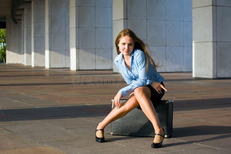 Junge Frau, die auf dem Aktenkoffer sitzt stockfotos