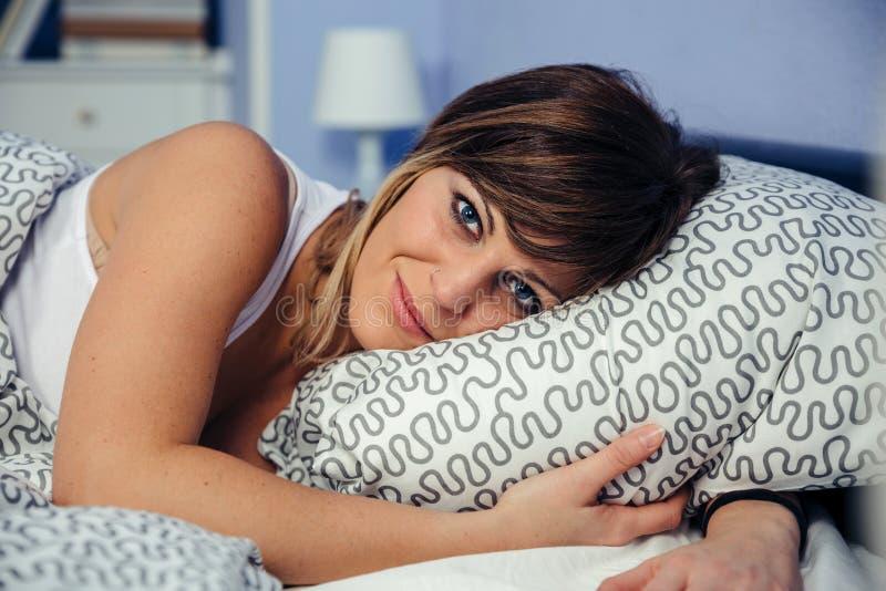Junge Frau, die auf dem Bett betrachtet Kamera liegt lizenzfreie stockfotografie