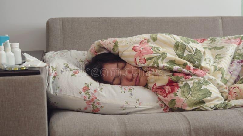 Junge Frau, die auf dem Bett eingewickelt in einer Decke liegt lizenzfreies stockfoto