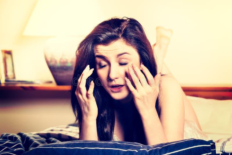 Junge Frau, die auf dem Bett liegt und Tablette verwendet Die Frau ist müde Augen lizenzfreie stockfotografie