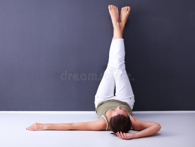 Junge Frau, die auf dem Boden mit den Beinen oben liegt lizenzfreie stockbilder