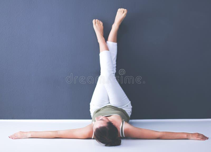 Junge Frau, die auf dem Boden mit den Beinen oben liegt stockbilder