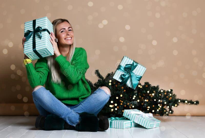 Junge Frau, die auf dem Boden nahe Tanne Weihnachtsbaum sitzt und über Geschenk, Geschenke und die Aufwartung eines Wunders träum stockfotos