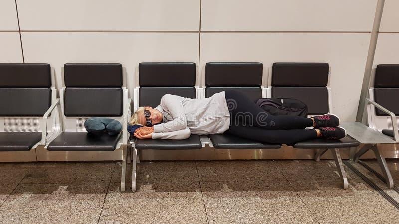 Junge Frau, die auf dem Flughafenabfertigungsgebäude stillsteht lizenzfreie stockfotos