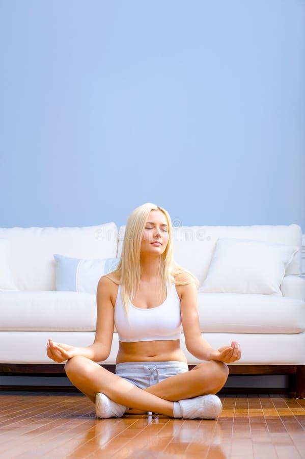 Junge Frau, die auf dem hölzernen meditierenden Fußboden sitzt lizenzfreies stockfoto
