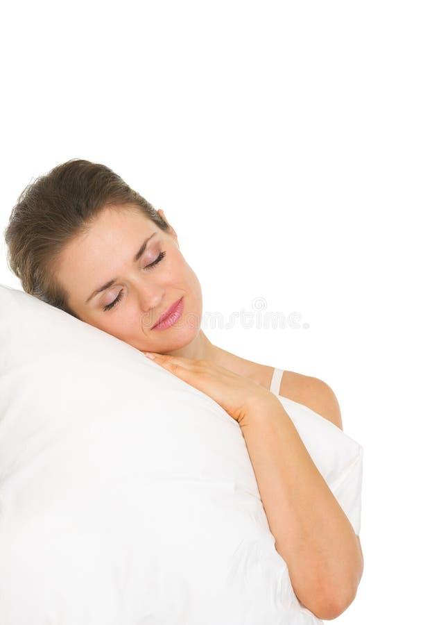 Junge Frau, die auf dem Kissen getrennt auf Weiß schläft lizenzfreies stockfoto