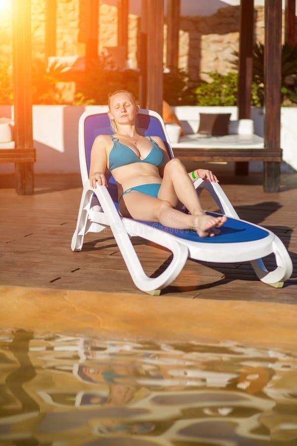 Junge Frau, die auf dem Klappstuhl durch den Swimmingpool am Erholungsort sich entspannt Sun-Aufflackern stockbild