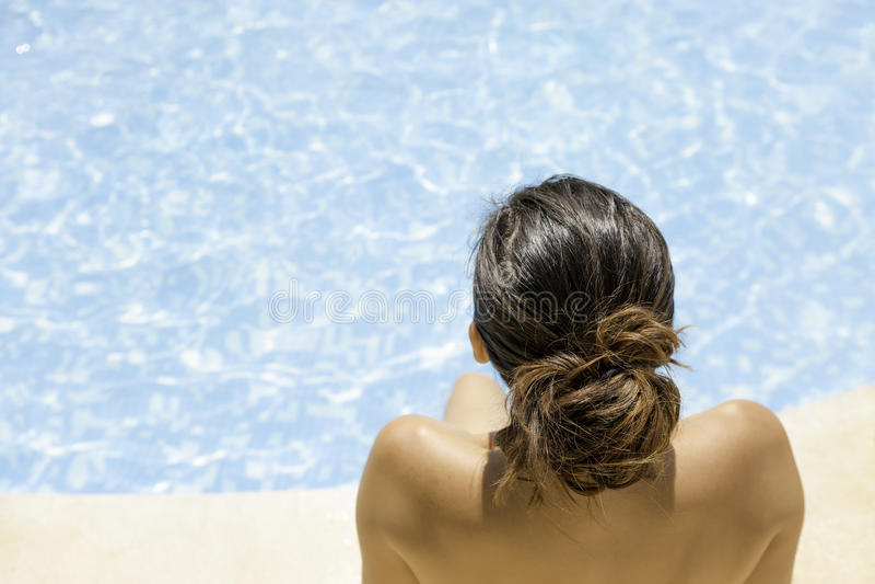Junge Frau, die auf dem Poolrand sitzt stockbilder