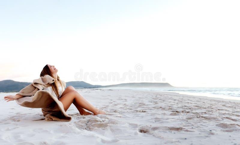 Junge Frau, die auf dem Sand sitzt lizenzfreie stockbilder