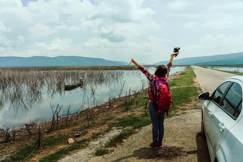 Junge Frau, die auf dem See in der Sommerzeit bleibt lizenzfreie stockfotografie