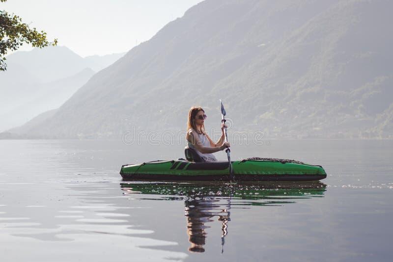 Junge Frau, die auf dem See Kayak f?hrt lizenzfreie stockfotografie