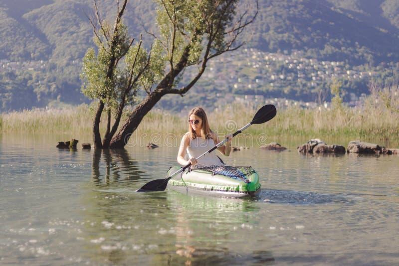 Junge Frau, die auf dem See Kayak f?hrt lizenzfreies stockbild