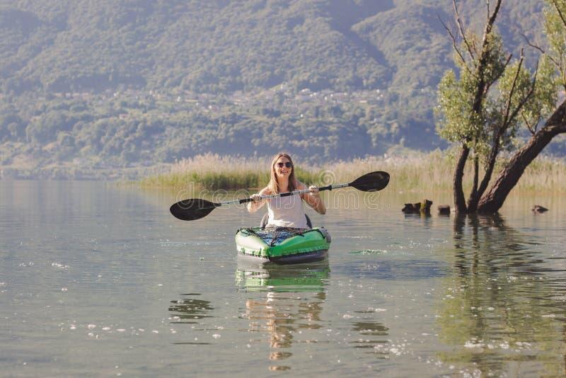Junge Frau, die auf dem See Kayak f?hrt stockbilder