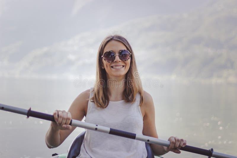 Junge Frau, die auf dem See Kayak f?hrt lizenzfreies stockfoto
